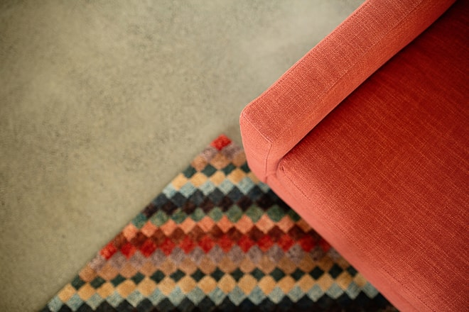 Interior design project photography. San Francisco Bay Area. Detail of red lounge chair and multicolor rug. Photographed by architectural photographer Ella Bessette