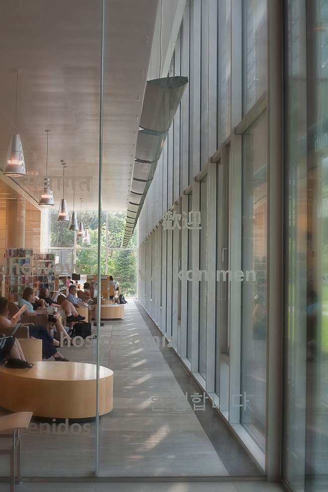 Glass entryway at Cambridge Library Boston MA. Architectural lighting by Selux. Photography by Ella Bessette Architectural photographer.