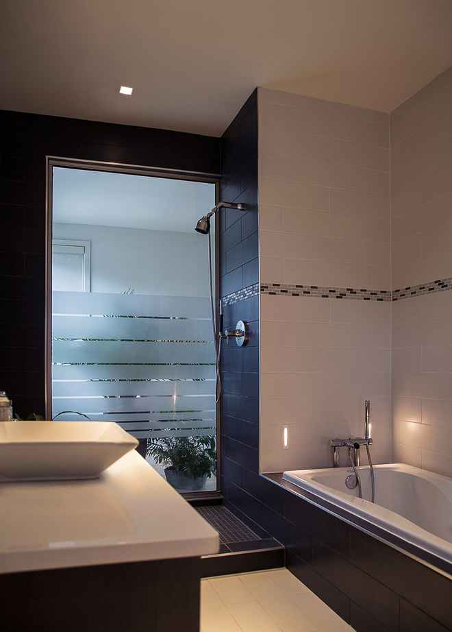 Modern black & white tiled bathroom in private residence with frosted glass walls by California architectural photographer Ella Bessette.