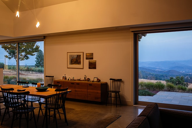 Private residence dining room floor to ceiling windows overlooking napa valley at dusk. Photographed by Ella Bessette architectural photographer.