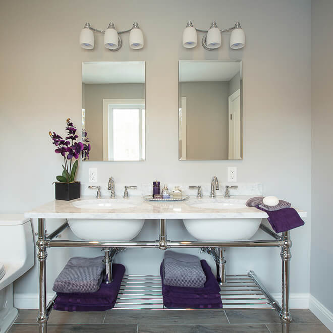 Interior design photography. Double sink in bathroom, purple accents & white marble. By architectural photographer Ella Bessette.